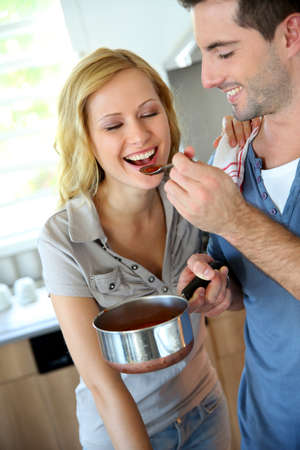 Woman tasting italian sauce cooked by boyfriend photo