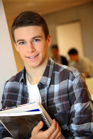 Student boy in class holding books photo