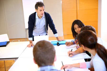 adult classroom: College teacher in class with group of students Stock Photo