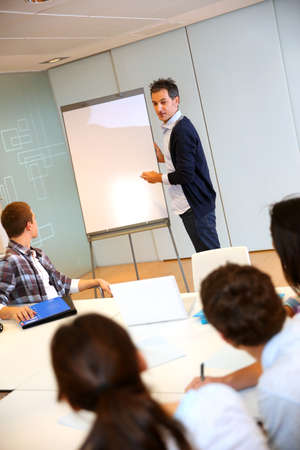 College teacher in class with group of students Stock Photo