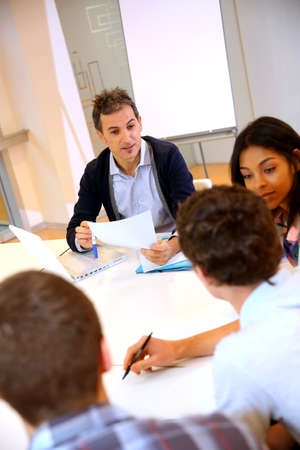 Teacher giving business presentation to students photo