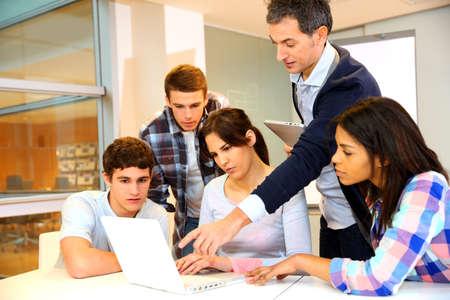 estudiantes universitarios: Grupo de estudiantes en formaci�n en inform�tica con el maestro