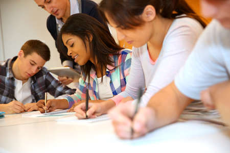 Group of teenagers in class writing an exam Stock Photo - 17335983