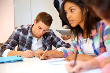 fill fill in: Group of teenagers in class writing an exam