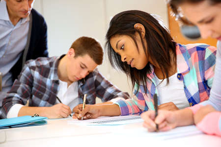 Group of teenagers in class writing an exam Stock Photo - 17335814