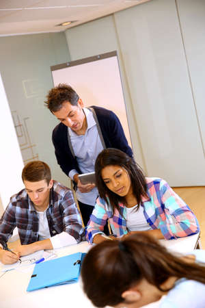 Teacher controlling group of students with paperwork photo