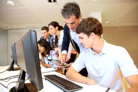 internship: Adult man helping student in classroom Stock Photo