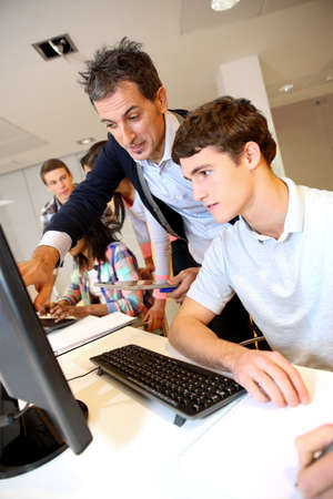 Adult man helping student in classroom photo