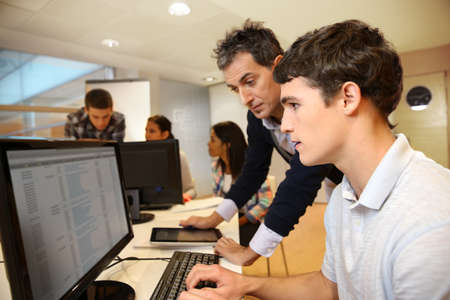 computer training: Adult man helping student in classroom Stock Photo