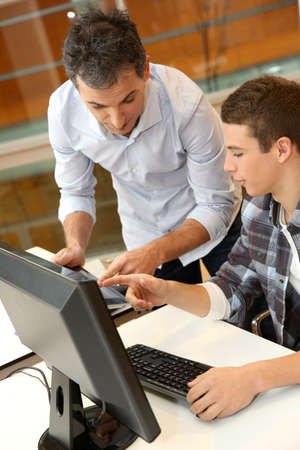 computer science classes: Adult man helping student in classroom Stock Photo
