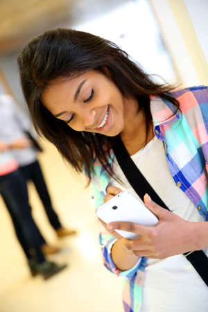 Cheerful student girl writing message on smartphone photo