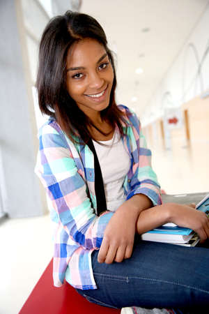 mixed race ethnicity: Cheerful student girl sitting on school bench Stock Photo