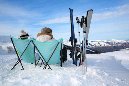 Couple of skiers relaxing in long chairs  Stock Photo - 17801723