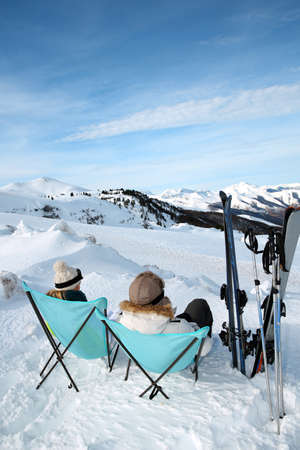 Couple of skiers relaxing in long chairs  photo