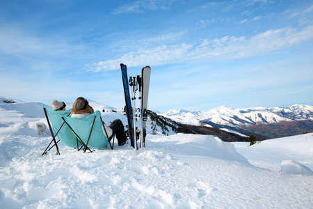 Couple of skiers relaxing in long chairs  Stock Photo - 17801711