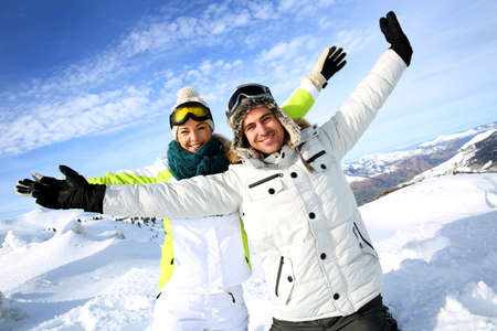 Cheerful couple of skiers stretching arms up  photo