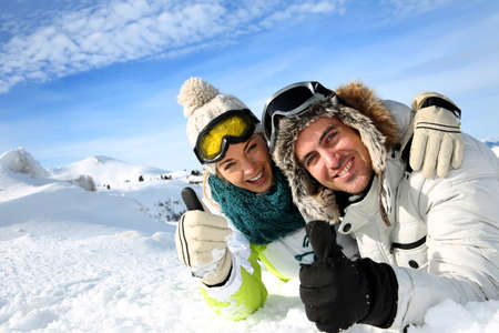 Couple of skiers laying down in the snow Stock Photo