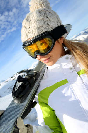 Portrait of woman at the mountain holding skis photo