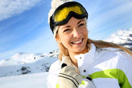 Portrait of cheerful blond woman at ski resort photo