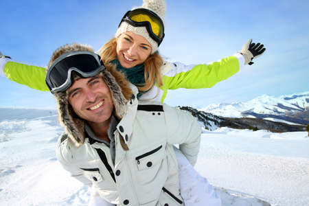 winter couple: Cheerful snowboarder holding girlfriend on his back Stock Photo