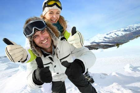 Cheerful snowboarder holding girlfriend on his back Фото со стока