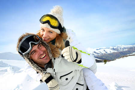 on skis: Skier at the mountain giving piggyback ride to girlfriend Stock Photo