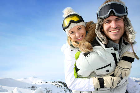 Cheerful snowboarder holding girlfriend on his back Stock Photo - 17801643