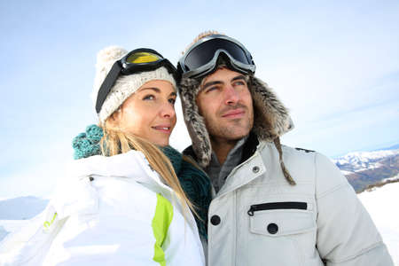 Portrait of couple of skiers looking at panorama photo
