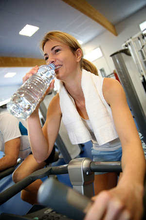 bodycare: Woman in fitness class drinking water from bottle