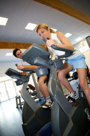 People exercising on bicycles in fitness gym photo