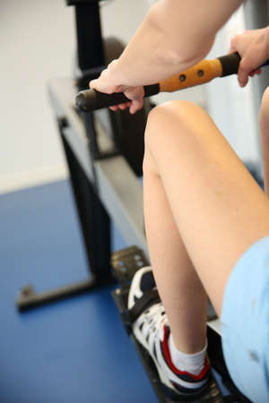 closeup on legs: Woman using rowing equipment in gym center