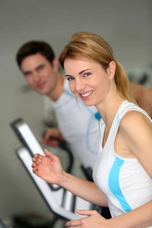 Couple in fitness gym using running belt photo