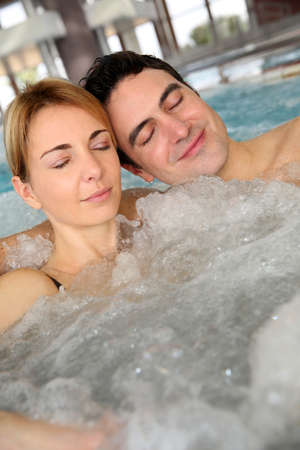 Couple relaxing in jacuzzi of spa center Stock Photo - 17801684