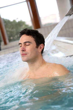 Man relaxing in massage pool photo