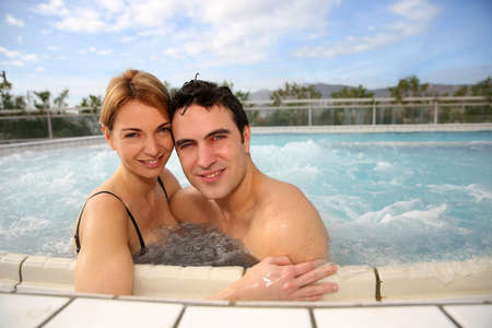Couple enjoying jacuzzi in spa center photo