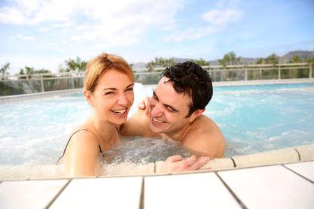 Couple enjoying jacuzzi in spa center