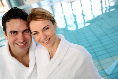 Portrait of couple in bathrobe standing in spa center
