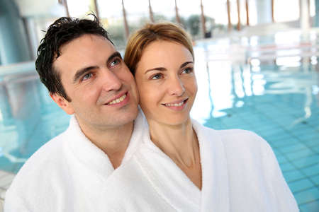 Portrait of couple in bathrobe standing in spa center photo
