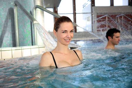 thalasso: Femme jouissant de douche hydrojet dans la piscine thermale Banque d'images