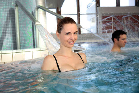 Woman enjoying hydrojet shower in spa pool photo