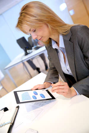 Businesswoman in office using electronic tablet photo
