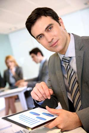 Businessman using digital tablet in office photo