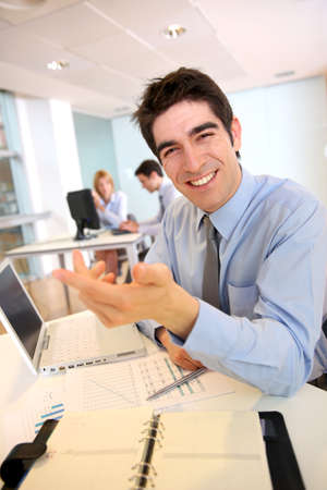 Cheerful salesman working on laptop computer photo