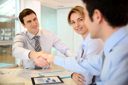 Businessman shaking hand to business partner photo