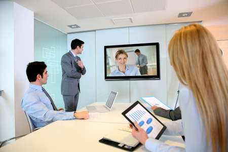 presentation screen: Business people attending videoconference meeting Stock Photo