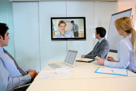 distant work: Business people attending videoconference meeting Stock Photo