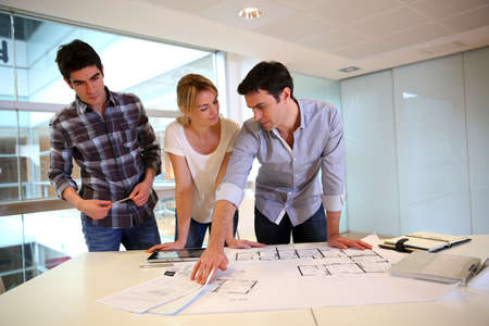 architecture project: Team of architects working on construction plans Stock Photo