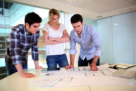 architect office: Team of architects working on construction plans Stock Photo