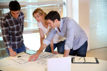 Team of architects working on construction plans photo