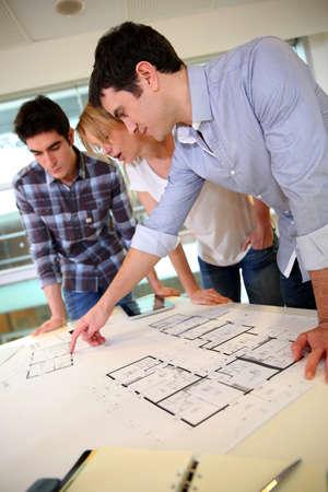 Startup business team working on blueprint photo